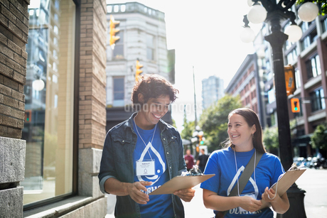 Smiling political young adults canvassing with clipboards on sunny urban sidewalkの写真素材 [FYI02324744]