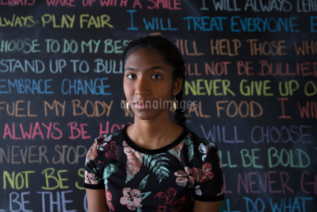 Portrait serious, confident Indian tween girl against wall with chalk textの写真素材 [FYI02324749]