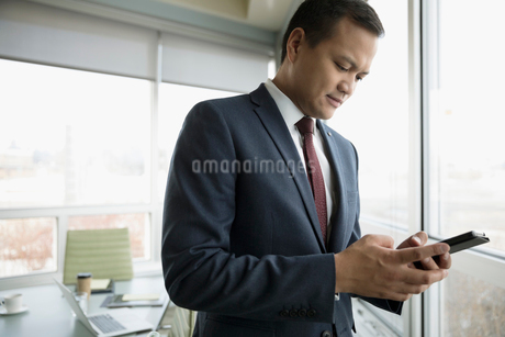 Businessman texting with smart phone in conference roomの写真素材 [FYI02324813]