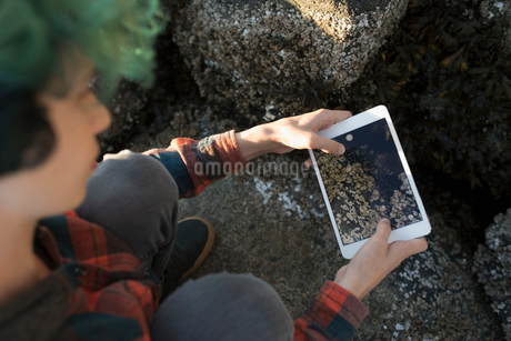 Overhead view boy with digital tablet camera photographing rocksの写真素材 [FYI02324816]