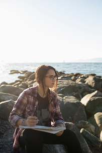 Teenage girl drawing in notebook on rocks on sunny ocean beachの写真素材 [FYI02324819]
