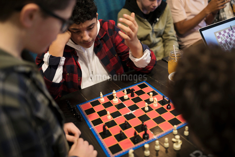 Tween boy friends playing chess at cafe tableの写真素材 [FYI02324842]