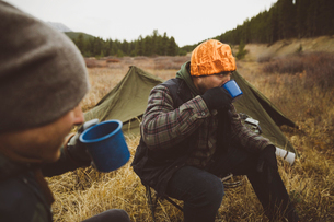 Male hunter friends drinking coffee outside tents at campsite in remote fieldの写真素材 [FYI02324845]