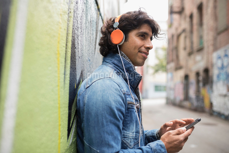 Smiling young man with headphones listening to music with smart phone on urban streetの写真素材 [FYI02324849]