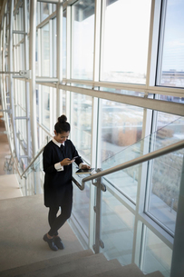 Businesswoman texting with smart phone on office stairsの写真素材 [FYI02324875]