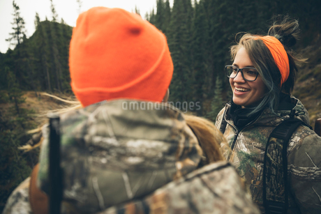 Smiling mother and daughter hunters in camouflage hunting, talking in forestの写真素材 [FYI02324903]