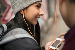Close up young couple sharing headphones, listening to music with smart phoneの写真素材 [FYI02324916]