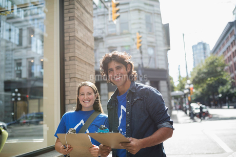 Portrait smiling political young adults canvassing with clipboards on sunny urban sidewalkの写真素材 [FYI02324919]