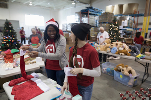 Smiling female volunteers in Santa hat filling Christmas stockings in warehouseの写真素材 [FYI02324929]
