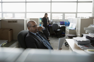 Businessman with paperwork talking on telephone in office cubicleの写真素材 [FYI02324930]