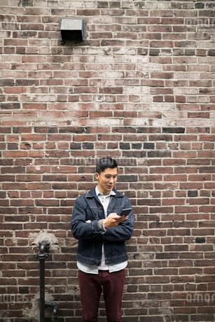 Man texting with smart phone along urban brick wallの写真素材 [FYI02324932]