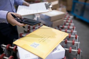 Male warehouse manager with smart phone scanning package QR code on production line conveyor beltの写真素材 [FYI02324942]
