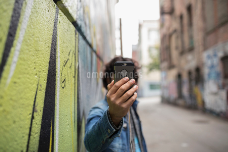 Young man with camera phone taking selfie along urban graffiti wallの写真素材 [FYI02324950]