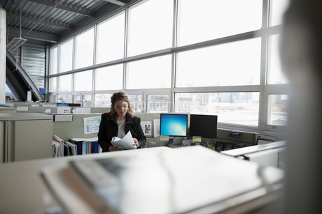 Focused businesswoman reading paperwork in office cubicleの写真素材 [FYI02324957]