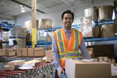 Portrait smiling, confident male warehouse manager with cardboard box in shipping warehouseの写真素材 [FYI02324976]