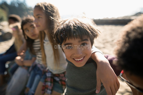 Portrait smiling boy on sunny beach with friendsの写真素材 [FYI02324986]