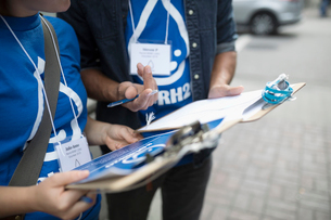 Close up political young adults canvassing with clipboards on sidewalkの写真素材 [FYI02324997]