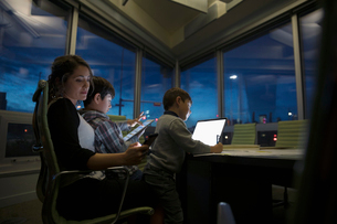 Dedicated mother working late with sons using digital tablet and laptop in dark conference roomの写真素材 [FYI02325006]