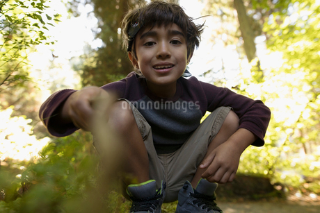 Portrait smiling boy with stick playing in woodsの写真素材 [FYI02325024]