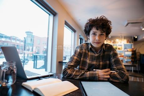 Portrait confident high school boy student studying, using stylus with digital tablet in cafeの写真素材 [FYI02325025]