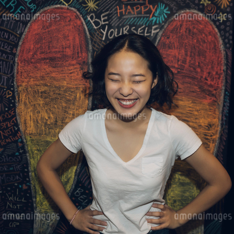Portrait enthusiastic, laughing Korean tween girl against wall with chalk wingsの写真素材 [FYI02325042]