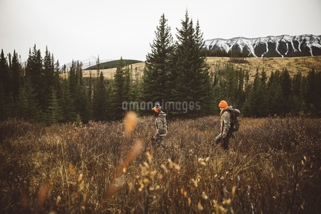Mother and daughter hunters in camouflage hunting, walking in remote field below mountainsの写真素材 [FYI02325045]