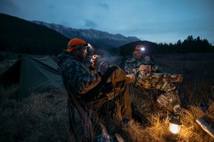 Male hunter friends in headlamps smoking pipes at campsite in remote field below mountains at nightの写真素材 [FYI02325060]
