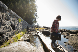 Boy with fishing tackle box standing on fallen log above ocean tidal poolの写真素材 [FYI02325084]