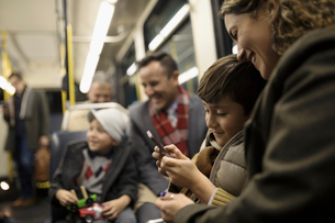 Latino mother and son texting with smart phone on busの写真素材 [FYI02325089]