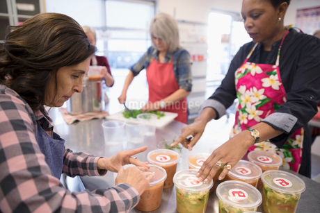 Female volunteers packaging soup containers in soup kitchenの写真素材 [FYI02325115]