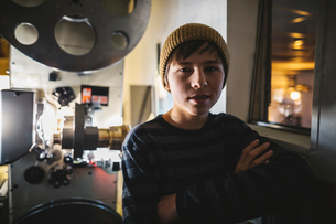 Portrait confident, serious, Caucasian boy projectionist operating film equipment in dark movie theaの写真素材 [FYI02325120]