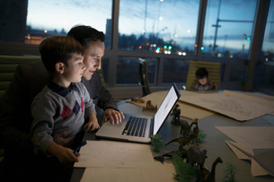 Father working late at laptop with son on lap in conference roomの写真素材 [FYI02325121]