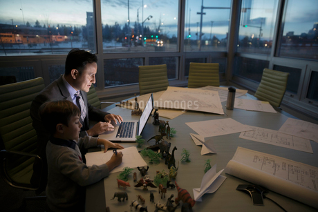 Boy coloring next to dedicated father architect working late at laptop in conference roomの写真素材 [FYI02325122]