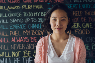 Portrait smiling, confident Korean tween girl against wall with chalk textの写真素材 [FYI02325137]