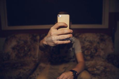 Tween boy taking selfie with camera phone in dark roomの写真素材 [FYI02325150]