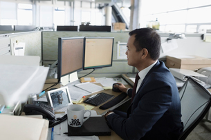 Focused businessman working at computers in office cubicleの写真素材 [FYI02325152]