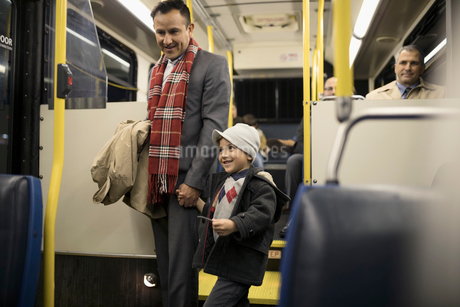Father and son holding hands on busの写真素材 [FYI02325163]