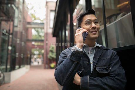 Man talking on cell phone on urban sidewalkの写真素材 [FYI02325177]