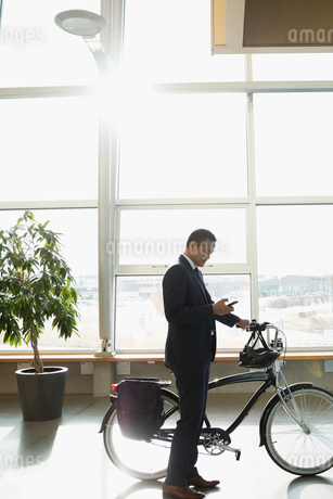 Businessman commuter with bicycle texting with smart phone in sunny office lobbyの写真素材 [FYI02325181]