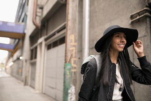 Smiling young woman in hat walking on urban streetの写真素材 [FYI02325195]