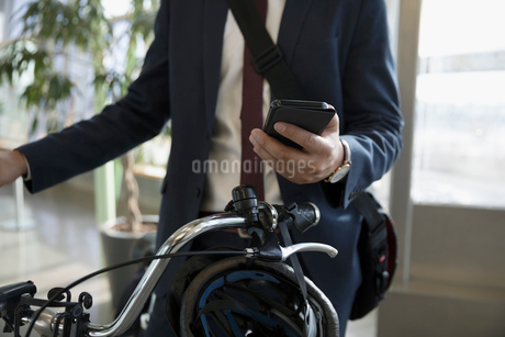 Close up businessman commuter with bicycle texting with smart phoneの写真素材 [FYI02325205]