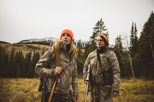 Mother and daughter hunters in camouflage carrying hunting rifles in remote field below mountainsの写真素材 [FYI02325207]