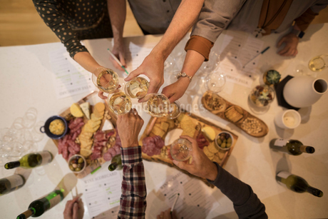 Overhead view friends toasting white wine glasses, enjoying wine tasting partyの写真素材 [FYI02325209]