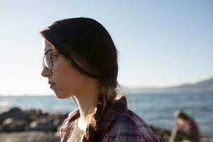 Serious, pensive brunette teenage girl with braid on sunny ocean beachの写真素材 [FYI02325220]