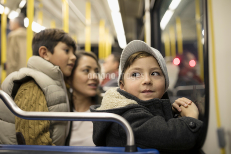 Cute boy riding bus with mother and brotherの写真素材 [FYI02325222]