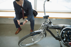 Businessman commuter texting with smart phone next to bicycleの写真素材 [FYI02325231]