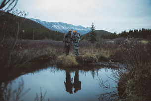 Male hunter friends tracking and hunting, looking down at water in remote fieldの写真素材 [FYI02325233]