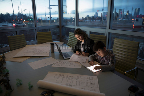 Boy using digital tablet next to dedicated mother architect working late in conference roomの写真素材 [FYI02325239]