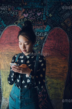 Asian tween girl texting with smart phone against wall with chalk angel wingsの写真素材 [FYI02325242]
