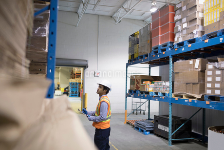 Male worker with clipboard checking inventory in distribution warehouseの写真素材 [FYI02325258]